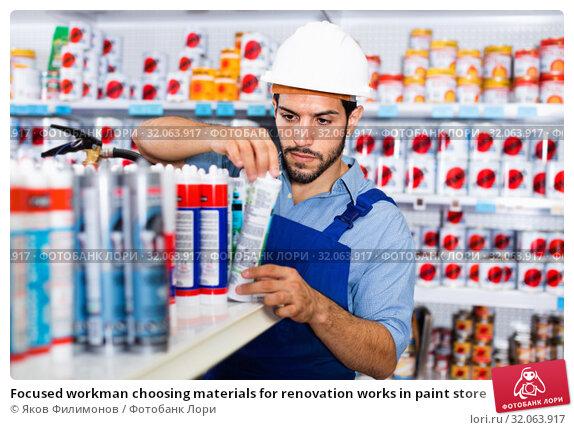Купить «Focused workman choosing materials for renovation works in paint store», фото № 32063917, снято 13 сентября 2017 г. (c) Яков Филимонов / Фотобанк Лори