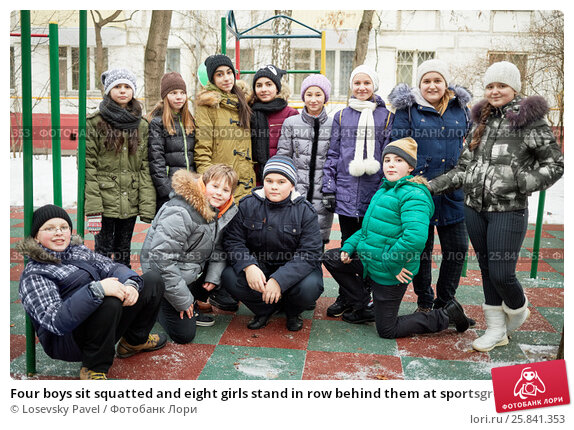 Купить «Four boys sit squatted and eight girls stand in row behind them at sportsground on winter day», фото № 25841353, снято 16 января 2015 г. (c) Losevsky Pavel / Фотобанк Лори