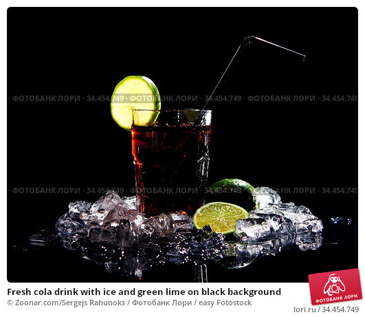 Fresh cola drink with ice and green lime on black background. Стоковое фото, фотограф Zoonar.com/Sergejs Rahunoks / easy Fotostock / Фотобанк Лори