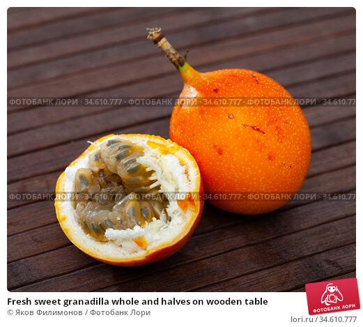 Fresh sweet granadilla whole and halves on wooden table. Стоковое фото, фотограф Яков Филимонов / Фотобанк Лори
