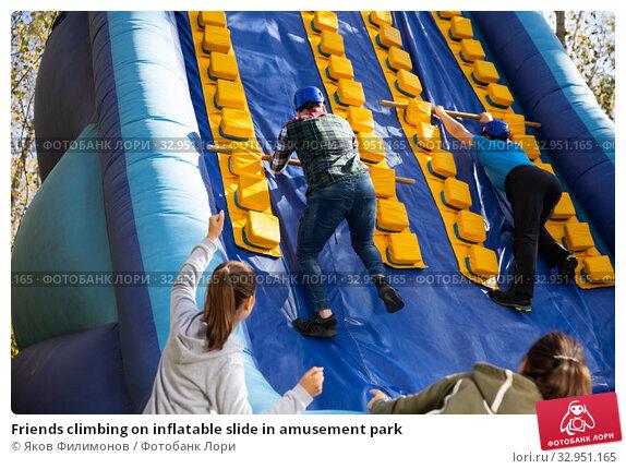 Friends climbing on inflatable slide in amusement park. Стоковое фото, фотограф Яков Филимонов / Фотобанк Лори