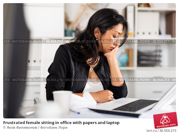 Frustrated female sitting in office with papers and laptop. Стоковое фото, фотограф Яков Филимонов / Фотобанк Лори