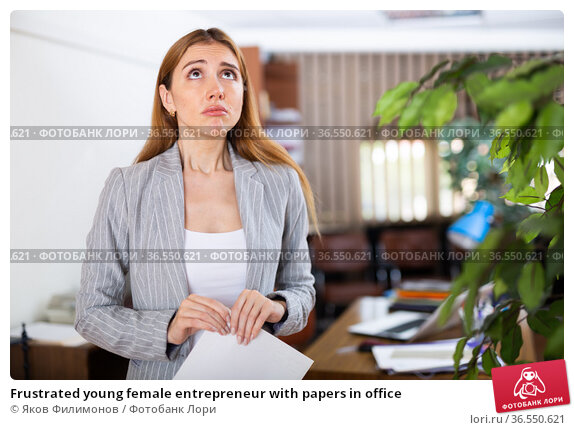 Frustrated young female entrepreneur with papers in office. Стоковое фото, фотограф Яков Филимонов / Фотобанк Лори