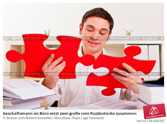 Geschäftsmann im Büro setzt zwei große rote Puzzlestücke zusammen. Стоковое фото, фотограф Zoonar.com/Robert Kneschke / age Fotostock / Фотобанк Лори