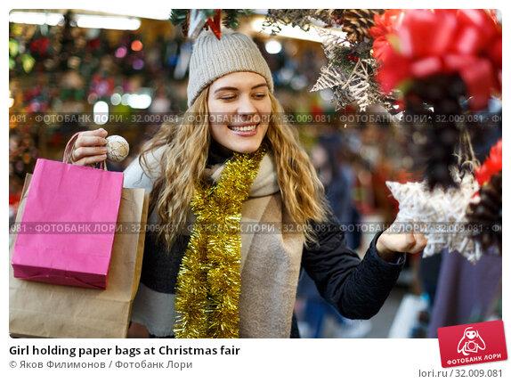 Купить «Girl holding paper bags at Christmas fair», фото № 32009081, снято 20 декабря 2018 г. (c) Яков Филимонов / Фотобанк Лори