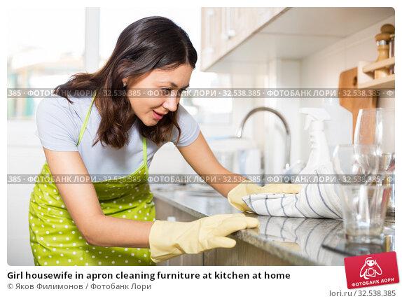 Купить «Girl housewife in apron cleaning furniture at kitchen at home», фото № 32538385, снято 18 апреля 2018 г. (c) Яков Филимонов / Фотобанк Лори
