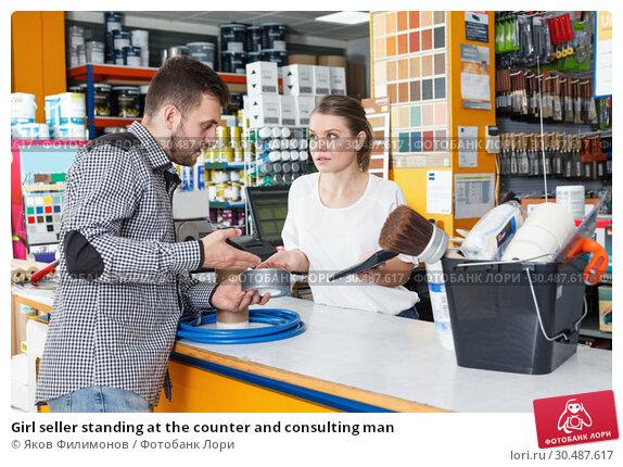 Купить «Girl seller standing at the counter and consulting man», фото № 30487617, снято 17 мая 2018 г. (c) Яков Филимонов / Фотобанк Лори