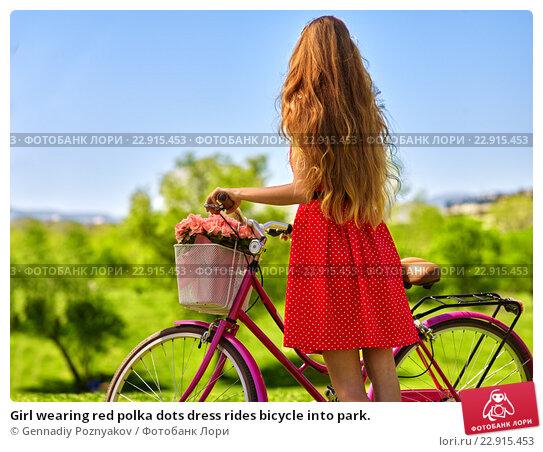 Купить «Girl wearing red polka dots dress rides bicycle into park.», фото № 22915453, снято 16 апреля 2016 г. (c) Gennadiy Poznyakov / Фотобанк Лори