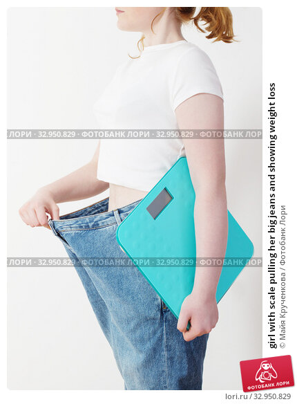 girl with scale pulling her big jeans and showing weight loss. Стоковое фото, фотограф Майя Крученкова / Фотобанк Лори