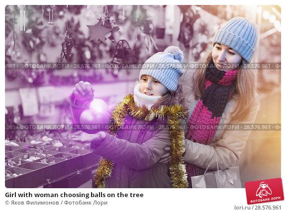 Купить «Girl with woman choosing balls on the tree», фото № 28576961, снято 19 декабря 2017 г. (c) Яков Филимонов / Фотобанк Лори