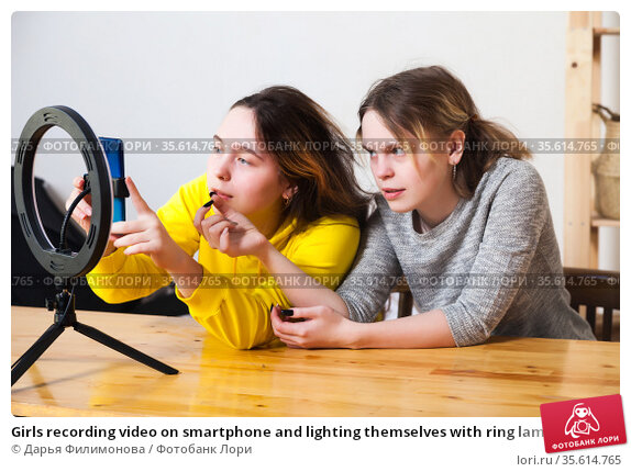Girls recording video on smartphone and lighting themselves with ring lamp. Стоковое фото, фотограф Дарья Филимонова / Фотобанк Лори