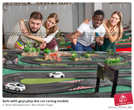 Girls with guys play slot car racing models. Стоковое фото, фотограф Яков Филимонов / Фотобанк Лори