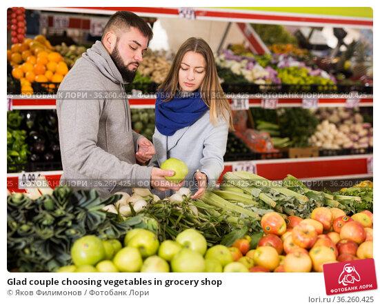 Glad couple choosing vegetables in grocery shop. Стоковое фото, фотограф Яков Филимонов / Фотобанк Лори