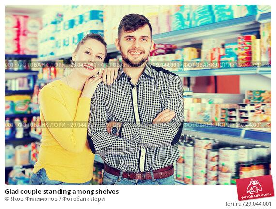 Купить «Glad couple standing among shelves», фото № 29044001, снято 20 января 2018 г. (c) Яков Филимонов / Фотобанк Лори