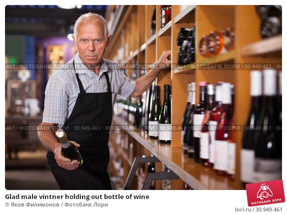 Купить «Glad male vintner holding out bottle of wine», фото № 30949461, снято 8 мая 2019 г. (c) Яков Филимонов / Фотобанк Лори