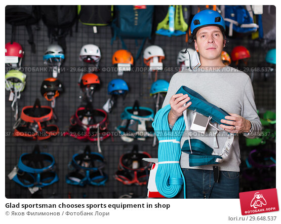 Купить «Glad sportsman chooses sports equipment in shop», фото № 29648537, снято 25 октября 2017 г. (c) Яков Филимонов / Фотобанк Лори