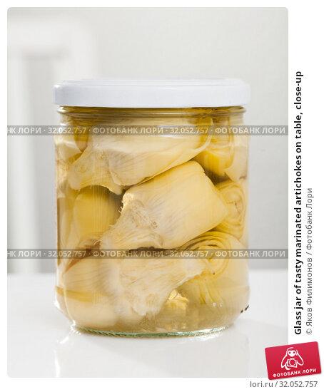 Glass jar of tasty marinated artichokes on table, close-up. Стоковое фото, фотограф Яков Филимонов / Фотобанк Лори