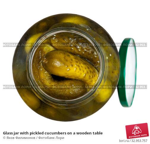 Glass jar with pickled cucumbers on a wooden table. Стоковое фото, фотограф Яков Филимонов / Фотобанк Лори