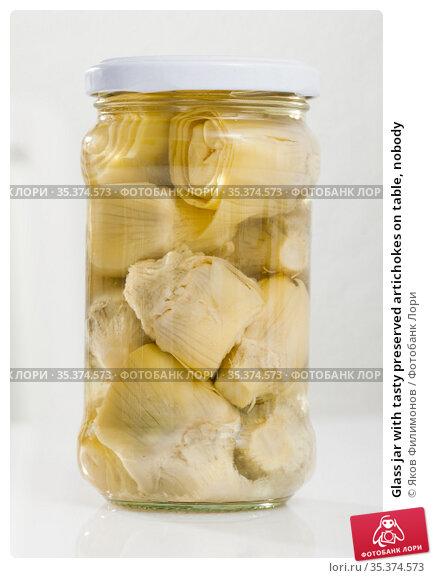 Glass jar with tasty preserved artichokes on table, nobody. Стоковое фото, фотограф Яков Филимонов / Фотобанк Лори