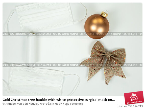 Gold Christmas tree bauble with white protective surgical mask on... Стоковое фото, фотограф Annebel van den Heuvel / age Fotostock / Фотобанк Лори