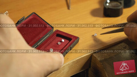 Goldsmith takes the jewel stone from the red box with the pincette slow motion. Стоковое видео, видеограф Denis Mishchenko / Фотобанк Лори