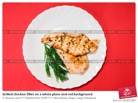 Grilled chicken fillet on a white plate and red background. Стоковое фото, фотограф Zoonar.com/***SALAUYOU YURY*** / easy Fotostock / Фотобанк Лори