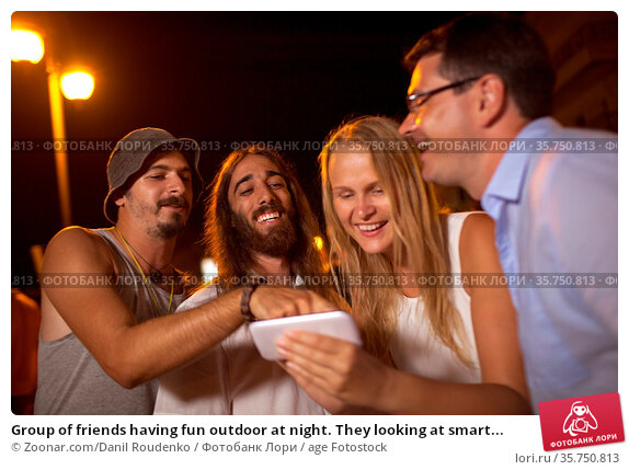 Group of friends having fun outdoor at night. They looking at smart... Стоковое фото, фотограф Zoonar.com/Danil Roudenko / age Fotostock / Фотобанк Лори