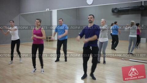 Group of happy adult people enjoying active social dances in modern dance studio. Стоковое видео, видеограф Яков Филимонов / Фотобанк Лори