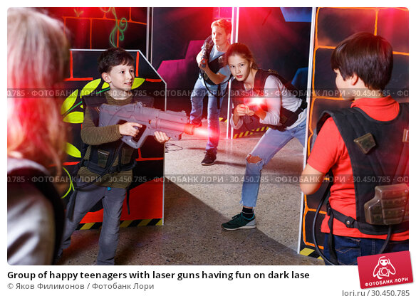 Group of happy teenagers with laser guns having fun on dark lase. Стоковое фото, фотограф Яков Филимонов / Фотобанк Лори