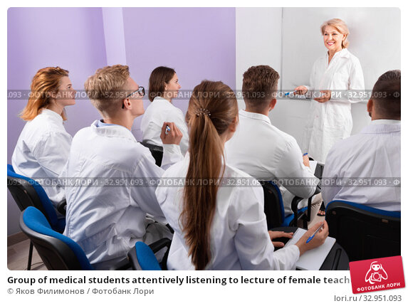 Group of medical students attentively listening to lecture of female teacher in classroom. Стоковое фото, фотограф Яков Филимонов / Фотобанк Лори