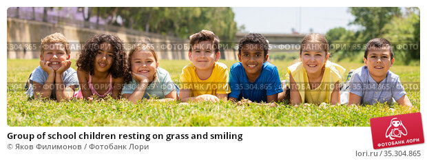 Group of school children resting on grass and smiling. Стоковое фото, фотограф Яков Филимонов / Фотобанк Лори