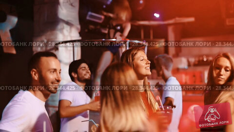 Купить «Group of smiling people clubbing in the night club with drinks», видеоролик № 28344425, снято 11 сентября 2017 г. (c) Яков Филимонов / Фотобанк Лори