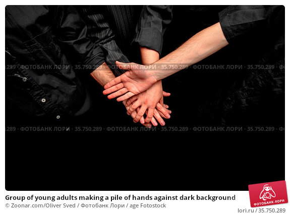 Group of young adults making a pile of hands against dark background. Стоковое фото, фотограф Zoonar.com/Oliver Sved / age Fotostock / Фотобанк Лори