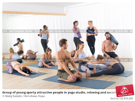 Group of young sporty attractive people in yoga studio, relaxing and socializing after hot yoga class. Healthy active lifestyle, working out in gym. Стоковое фото, фотограф Matej Kastelic / Фотобанк Лори