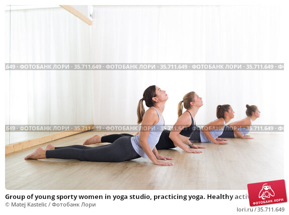 Group of young sporty women in yoga studio, practicing yoga. Healthy active lifestyle, working out indoors in gym. Стоковое фото, фотограф Matej Kastelic / Фотобанк Лори