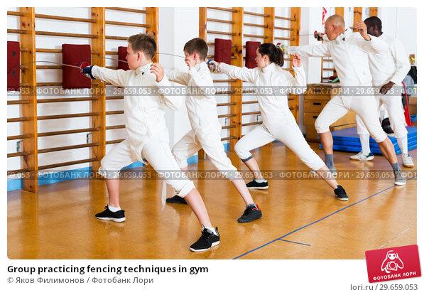 Купить «Group practicing fencing techniques in gym», фото № 29659053, снято 30 мая 2018 г. (c) Яков Филимонов / Фотобанк Лори