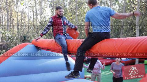 Guys having funny wrestling by pillows on inflatable beam in outdoor amusement playground. Стоковое видео, видеограф Яков Филимонов / Фотобанк Лори