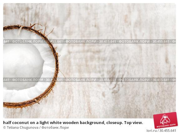 half coconut on a light white wooden background, closeup. Top view. Стоковое фото, фотограф Tetiana Chugunova / Фотобанк Лори