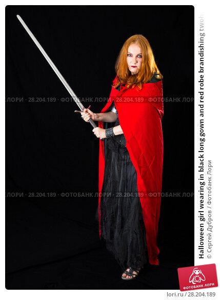 Купить «Halloween girl wearing in black long gown and red robe brandishing twohanded sword», фото № 28204189, снято 6 июля 2017 г. (c) Сергей Дубров / Фотобанк Лори