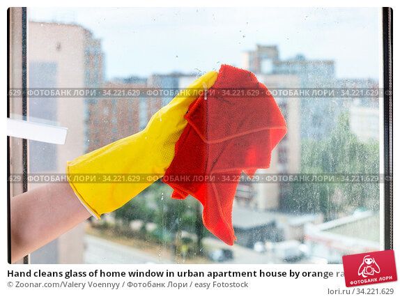 Hand cleans glass of home window in urban apartment house by orange rag. Стоковое фото, фотограф Zoonar.com/Valery Voennyy / easy Fotostock / Фотобанк Лори