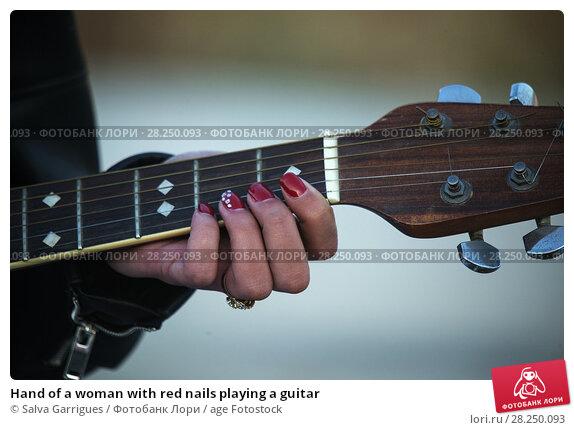 Купить «Hand of a woman with red nails playing a guitar», фото № 28250093, снято 17 ноября 2017 г. (c) age Fotostock / Фотобанк Лори