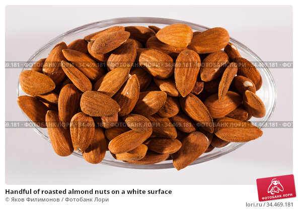 Handful of roasted almond nuts on a white surface. Стоковое фото, фотограф Яков Филимонов / Фотобанк Лори