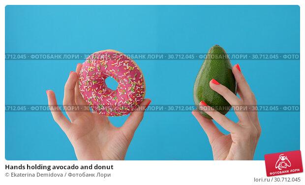 Hands holding avocado and donut. Стоковое фото, фотограф Ekaterina Demidova / Фотобанк Лори