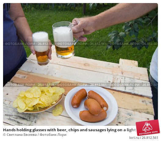 Купить «Hands holding glasses with beer, chips and sausages lying on a light wooden boards, people relax in the weekends, Octoberfest», фото № 26812561, снято 19 августа 2017 г. (c) Светлана Евсеева / Фотобанк Лори