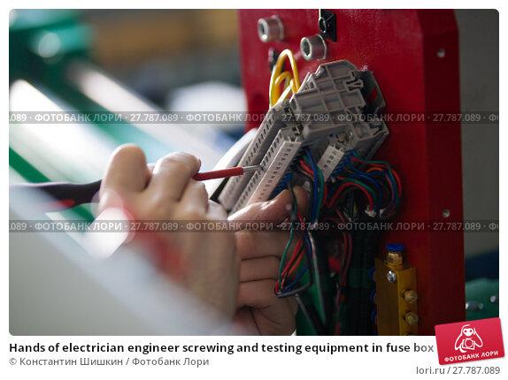 Купить «Hands of electrician engineer screwing and testing equipment in fuse box», фото № 27787089, снято 12 февраля 2018 г. (c) Константин Шишкин / Фотобанк Лори