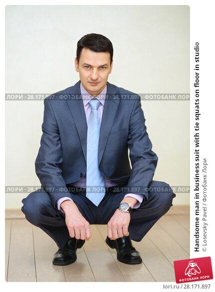 Купить «Handsome man in business suit with tie squats on floor in studio», фото № 28171897, снято 28 апреля 2016 г. (c) Losevsky Pavel / Фотобанк Лори