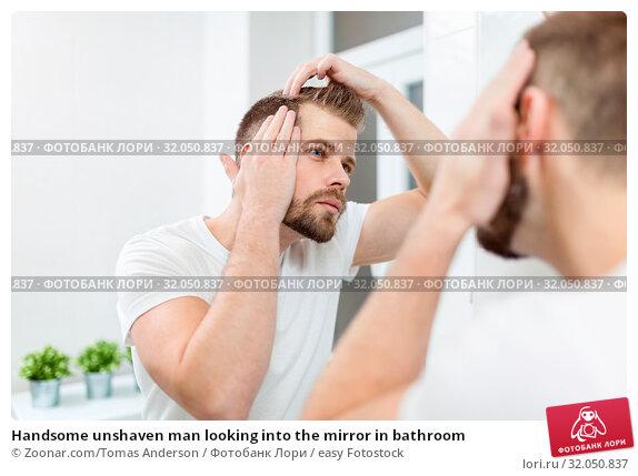 Handsome unshaven man looking into the mirror in bathroom. Стоковое фото, фотограф Zoonar.com/Tomas Anderson / easy Fotostock / Фотобанк Лори
