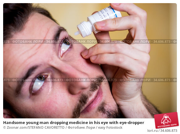 Handsome young man dropping medicine in his eye with eye-dropper. Стоковое фото, фотограф Zoonar.com/STEFANO CAVORETTO / easy Fotostock / Фотобанк Лори