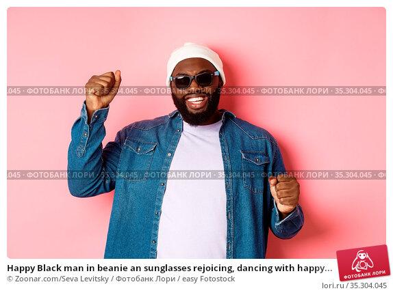 Happy Black man in beanie an sunglasses rejoicing, dancing with happy... Стоковое фото, фотограф Zoonar.com/Seva Levitsky / easy Fotostock / Фотобанк Лори