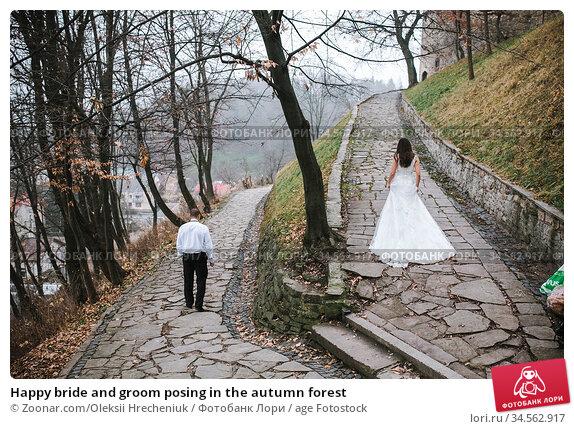 Happy bride and groom posing in the autumn forest. Стоковое фото, фотограф Zoonar.com/Oleksii Hrecheniuk / age Fotostock / Фотобанк Лори